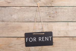 For-rent-sign-hanging-on-wood-wall