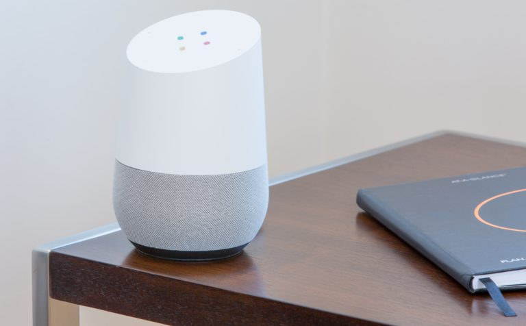White Google Home on dark wooden table