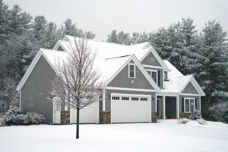 Grey single storey home in winter with tree in front