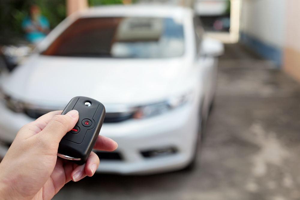 Person using key fob to unlock a white car