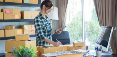 woman wearing plaid shirt with hair in bun and glasses packages items for delivery in her home office. packages are all around her on desk and shelving unit.