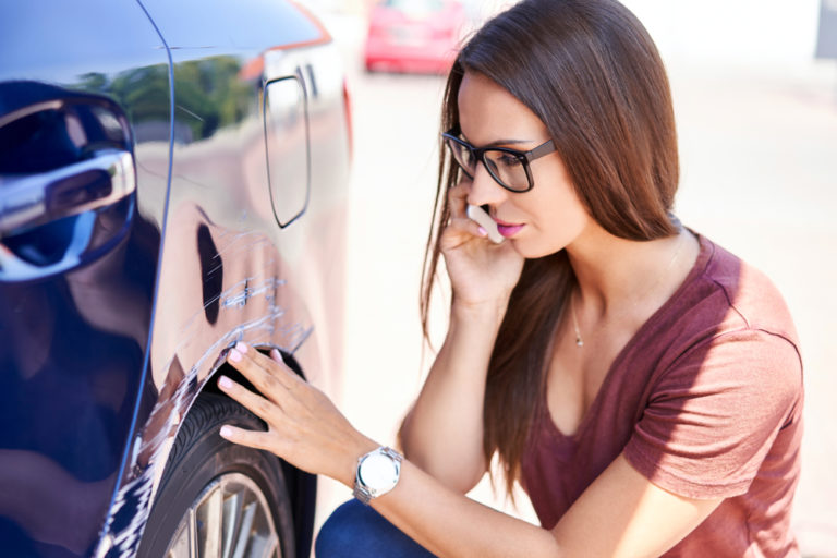 woman with long brown hair and glasses inspects the scratches on her car while talking on the phone