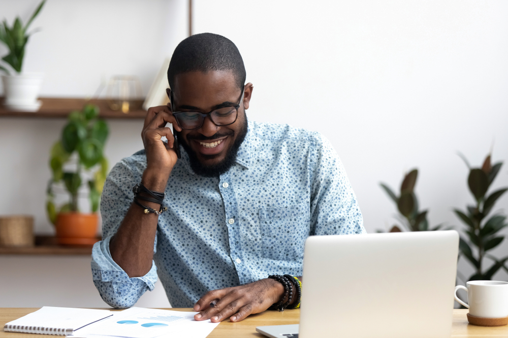 man talks on phone while sitting at desk in home office