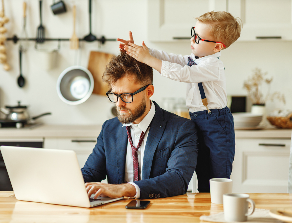 businessman works at computer while small child plays with his hair